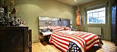 Double bed with American flag as bedspread in green bedroom