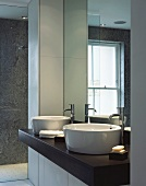 Washstand with two white ceramic sinks on a dark wooden counter below mirror