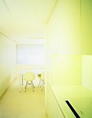 White fitted kitchen in niche of open-plan dining room
