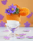 An egg in an egg cup with a crocheted egg cosy decorated with flowers