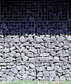 Gabion fence of stacked stone in wire cages