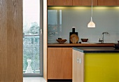 View through open door into modern kitchen with counter and yellow painted fronts