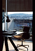 Desk with modern office swivel chair in front of ceiling-height balcony window with view of city