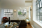 Breakfast in loft-style living space with industrial windows and black metal glazing bars