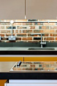 Detail of modern kitchen unit in front of an old brick wall with electrical wiring