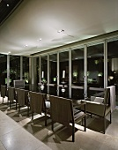 Modern dining table with elegant chairs in glass-walled living space at night
