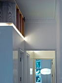 Cubist construction with wooden shelving on top in traditional room and open door with view of standard lamp