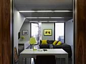 Blick durch offene Tür auf weissen Arbeitstisch und graues Sofa