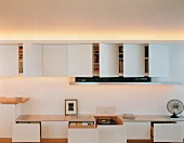 Modern, white wall-mounted cupboards and low storage units with opened doors and drawers