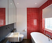 Modern bathroom with bathtub against red mosaic tiles and basin under mirrored cupboard