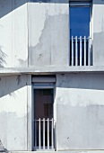 Concrete facade with French windows and railings