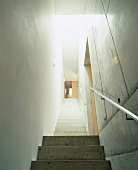 Narrow stairwell with treads and walls of exposed concrete