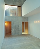 Empty foyer with large transom window and open concrete doorways leading to wooden doors