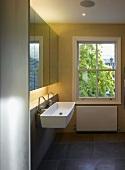 Schlichter moderner Badraum mit Waschtisch und Armatur unter Spiegelschrank