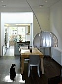 Curved lamp in front of dining area with rustic wooden table and open kitchen