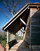 Wooden house with rustic porch over entrance area with steps