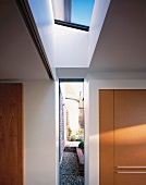 Fitted wardrobe with wooden door in niche of foyer with skylight and floor to ceiling window