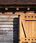 Rustic wooden door in front of weathered wooden house facade