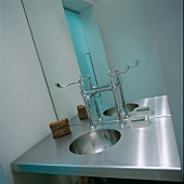 Stainless steel designer washstand with taps in front of mirror