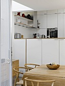 Open sliding door in perforated metal with view into kitchen with classic chairs in dining area