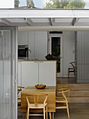 View of dining area with classic chairs and a modern kitchen through open sliding terrace door