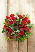A bunch of eucalyptus, roses, ivy and skimmia hanging on a wooden wall