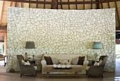 Sofagarnitur mit rustikalem Couchtisch vor gebogenem Raumteiler aus stilisierten Natursteinen in südländischer Hütte