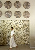 Woman walking through meditative room - wall decorations hanging on lintel above doorway and view of stone wall beyond
