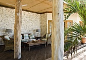 View between rustic wooden columns of wicker chairs and coffee table on roofed terrace of tropical villa