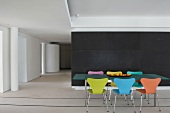 Dining area with colourful 50s designer chairs in front of dark partition in purist loft; table legs on metal rails in white flooring