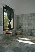 Reclaimed stone tiles and sunken marble bathtub in bathroom
