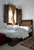 Antique wooden bed with leather headboard below window