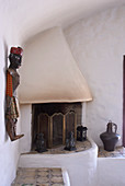 Masonry corner fireplace decorated with lanterns and sculpture on wall