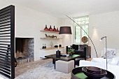 Designer living room with arc lamp above dark brown coffee table in front of open fireplace