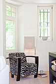 Retro armchair with zebra-patterned upholstery in front of modern standard lamp in corner
