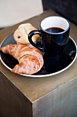 Cup of coffee, croissant and muffin on black plate