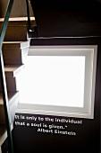 Anschnitt einer steilen Holztreppe und unter einem Fenster ein Sinnspruch von Albert Einstein in weisser Schrift auf schwarzer Wand