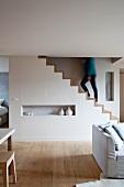 weiße Maisonette-Wohnung im modernen skandinavischen Stil mit gewachstem Dielenboden; skulpturaler Treppenblock mit gehender Frau im Hintergrund