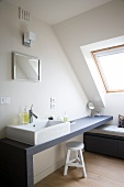 Optimal genutzte Dachschräge - Bad im schlichten skandinavischen Stil mit rechteckigem Aufsatzbecken auf graublauer Waschtischplatte und Stauraum unter einer Sitzbank