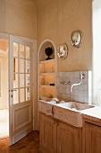 Stone sink next to open glass lattice door in rustic kitchen