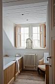 View through open door into bathroom with bathtub next to dormer window