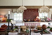 Vintage pendant lamps with fabric lampshades above set table and antique wooden chairs in rustic kitchen