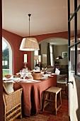 Gedeckter Esstisch mit lachsrotem Tischtuch passend zur Wandfarbe und Blick durch breiten Rundbogen ins Wohnzimmer