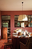 Pendant lamp with white lampshade above set table in dining room with dusky pink wall and integrated interior windows
