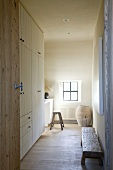 Open interior door with view into simple, narrow room with fitted wardrobes and workspace
