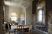 Mixture of styles in open-plan living-dining room with rustic wooden table and antique chairs opposite Rococo console table below gilt-framed mirror