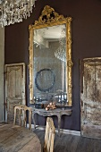 Tall mirror with Baroque gilt frame above Rococo console table against wall painted dark grey flanked by unrestored wooden doors in rustic interior