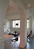 View of barstool and white sofa combination through open column structure in loft-style interior