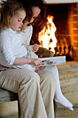 A mother and daughter reading a book in front of a fireplace