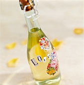 A bottle of sparkling wine decorated with flowers and the word LOVE